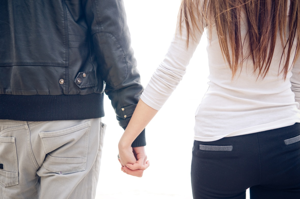 Young couple holding hands. White background.