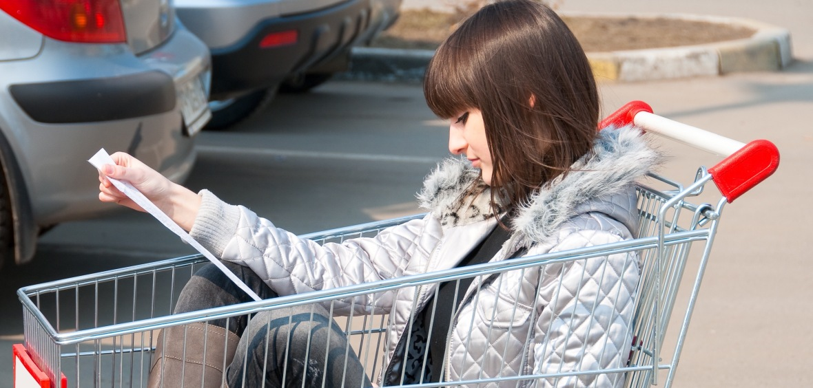 Pretty girl sits in a cart and reads receipt from supermarket